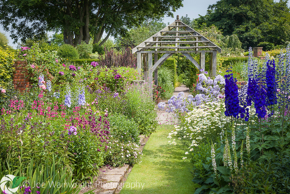 Delphiniums, penstemons, clematis and phlox provide a climax of colour in the Sundial Garden at Wollerton Old Hall Garden, Shropshire.