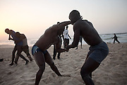 "Hard training on the beach with fight for two professional Lamb's wrestlers from Ecurie Fass, one of the most famous team in Senegal, Papa Sow (left) and Maabsa (right). North Dakar, Senegal, on tuesday, April 07 2009.....""Lamb, the wolof word for fight, is a very popular type of African wrestling in Senegal. This ""lutte traditionelle"" has been transformed into a national cult, drawing massive following next only to football. Senegalese wrestlers are among the best-known national sports figures. The senegalese fight form allows blows with the hands (frappe), the only of the West African to do so. The lutteurs wrestle in a sandy arena and attempt to win by making their opponent's knees, shoulder, or back touch the sand. Matches are festive and lively occasions, with music, dancing, and praise singing for the athletes; the actual wrestling bouts, however, are often over within a few seconds. Presently, wrestling is arranged by business-promoters who offer prizes for the winners..The sport has produced its own legends, names such as Yékini, Tyson and Bombardier (stage names) are celebrities in Senegal. In particular Mohammed Ndao, aka Tyson,  the 34-year-old leader of the Boul Falé generation of Pikine, a Dakar suburb, did not only revolutionise the sport, by carving his own group identity, and upsetting the old guard, but he is also credited with insisting on commensurate remuneration for the wrestlers. A ""combat"" could start from 10 million CFA francs (about 20,000 US dollars) to 65 million CFA francs. (about 130,000 dollars). The phenomenal success is such that stakeholders are already talking about building a separate stadium for the sport in the country."""