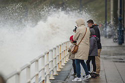 © London News Pictures. 22/10/2017. Aberystwyth,UK. A family watch large waves continue to crash in to the promenade. After two days of winds, the tail end of storm Brian is still battering the seafront and promenade in Aberystwyth on the Cardigan Bay coast of west wales. Photo credit: Keith Morris/LNP