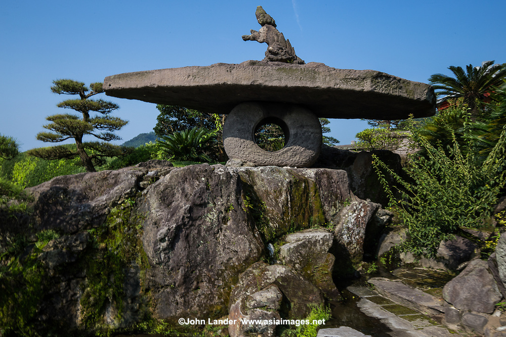 Sengan-en Garden is a  daimyo strolling garden in Kagoshima. It's most striking feature is its use of the volcano at Sakurajima beyond Kagoshima Bay as background scenery. The garden itself is made up of small ponds, streams, rockeries and sculpted terrain. The garden was created in 1658 by the powerful feudal Shimazu Clan who ruled Satsuma Kagoshima for 700 years and continued to be influential into the modern era as some of the earliest adopters of Western technology.  Sengan-en piggybacks on the  UNESCO status of the adjacent Shoko Shusiekan and the Ijinkan which are part of the Meiji Japan Industrial agglomeration of UNESCO World Heritage sites.
