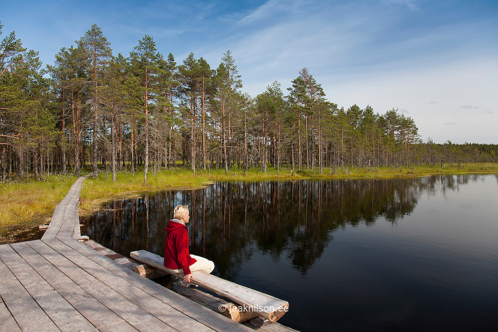 Young Woman Sitting by Lake, Viru Bog, Lääne-Viru County, Estonia, Europe