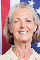 Portrait of smiling senior woman against American flag