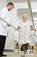 Technician looking at senior woman having ambulatory therapy