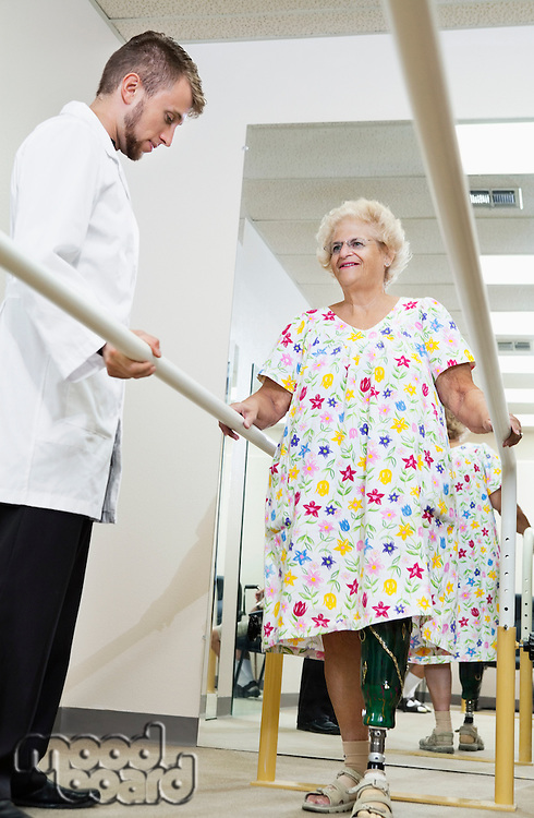 Technician looking at senior woman having ambulatory therapy