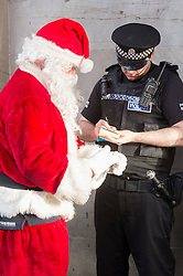 A police officer for Police Scotland has a quiet word with Ricky McConnell who dressed as Santa and waved at passeres by from the Duke of Wellington on the statue in Royal Exchange Square Glasgow<br />