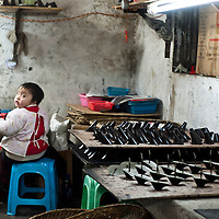 Chongqing, China - 31 December 2010: a small child have lunch sitting next to shoe heels in a textile factory. The children often linger and play around and inside the factories while their parents work. <br /> According to a report published by Bank of America Merrill Lynch's David Cui, titled 'Not So Trivial Facts', China has produced in 2010 a total of 12.6 billion pairs of shoes which means 9.4 pairs of shoes per person, compared with 1.3 pairs in the rest of the world (63.0 percent of global total).