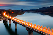 Lighted bridge at night over a lake