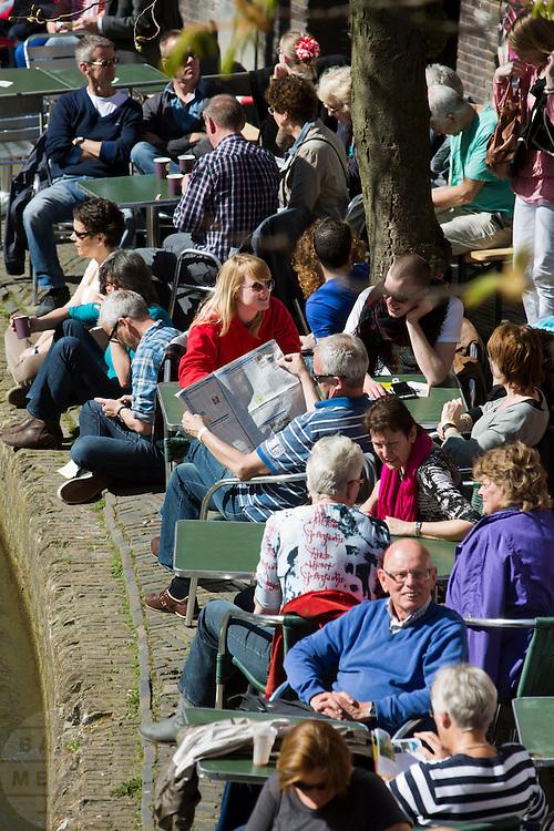Mensen genieten op een overvol terras aan de Oudegracht in Utrecht van het mooie weer.<br /> <br /> People are enjoying the nice weather in Utrecht on the terrace.