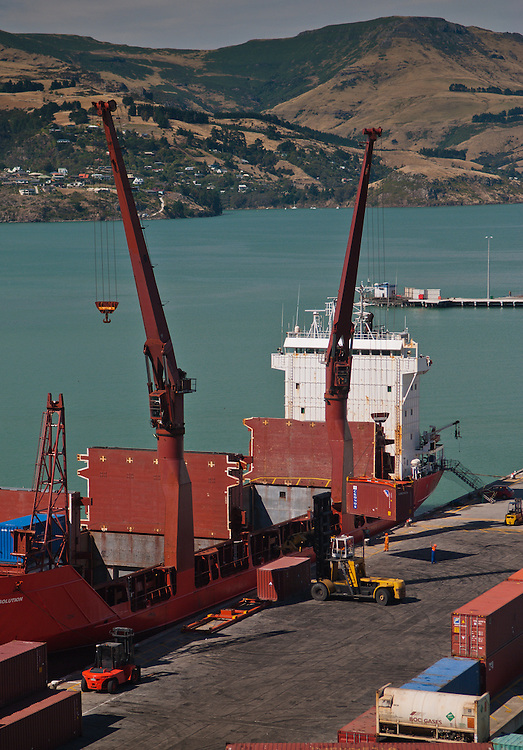 Dock workers unload containers from cargo vessel Spirit of Resolution onto the wharf at Lyttelton Harbour, New Zealand, with Banks Peninsula hills in the background