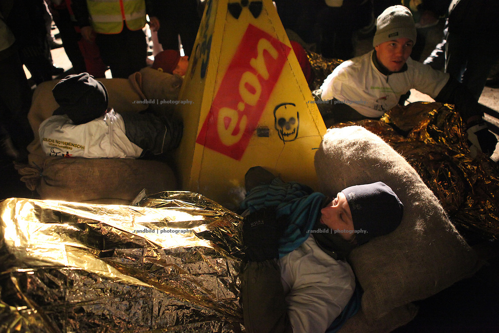 Unrest in Lüchow-Dannenberg. Local farmers are chained inside a concrete block and an important road. Thousands of people demonstrate against a transport of 11 Castor containers filled with high radioactive waste to Gorleben, Lower Saxony, Germany. The protest takes place shortly after the governments unpopular decision to extend the period of operation for german nuclear power plants for an additional decade.