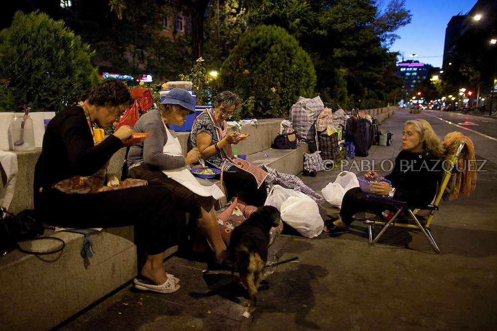 (L-R) Antonia Sastre Castilla 45, her mother Carmen Castilla 77, and her sisters Carmen Aurora 49 and Rosa Maria 46, have a salad for dinner in the street on September 3, 2012, in Madrid, Spain. The family of four were evicted from the flat they were renting on April 24th, after Rosa lost her job and the main income of the family. They couldn't afford to pay anymore their rent. Social Services provided with temporally shelter for 15 days, but after that they found themselves living in the street. They have wrote to the Spanish Prime Minister, the King, the Prince and the Queen of Spain, the President of Madrid but all answers received were saying that they were really sorry about their situation but there was nothing they could do on their hands, referring them to the Social Services. They have registered their census in a piece of street of Madrid. Neighbors often give them a hand providing food, blankets, charging mobiles or making their laundry. The family lives of their mother's widow's pension, some money they get from visually impaired Antonia's welfare allowance, and whatever income the sister Carmen Aurora can get working as a concierge at a nearby building.They sleep rough in a store front door nearby. Carmen 77, with back and heart problems, sleeps sitting on her armchair as she is not able to stand up from ground level if she would sleep on top of a mattress.