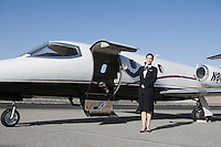 Female flight attendant standing in front of private jet on runway.