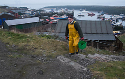 © Licensed to London News Pictures. <br /> 17/03/2015. <br /> <br /> South Gare, Teesside.<br /> <br /> A fisherman carrying bait for fishing walks up steps from Paddy's Hole at South Gare on the mouth of the River Tees.<br /> <br /> Photo credit : Ian Forsyth/LNP