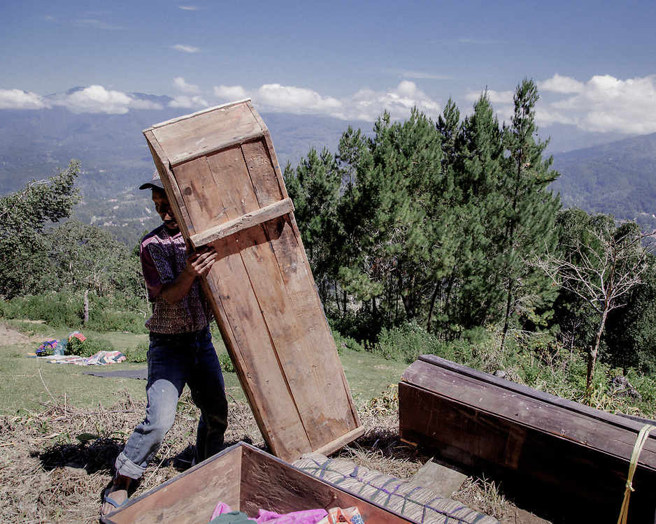 A family member opens the coffin of a dead relative to be dried under the sun.<br />