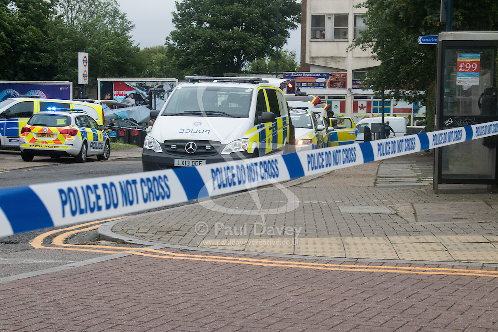 """Kensal Green, London, May 31st 2016. Armed police in body armoured protective headgear seal off Kensal Green tube and overground station in North West London in what is described as a """"security incident"""". PICTURED: Police vehicles behind the cordon outside Kensal Green Tube station."""