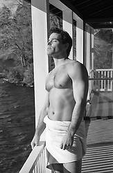 shirtless beefy man in a towel standing on a lake house porch