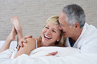 Middle-aged couple lying on bed laughing