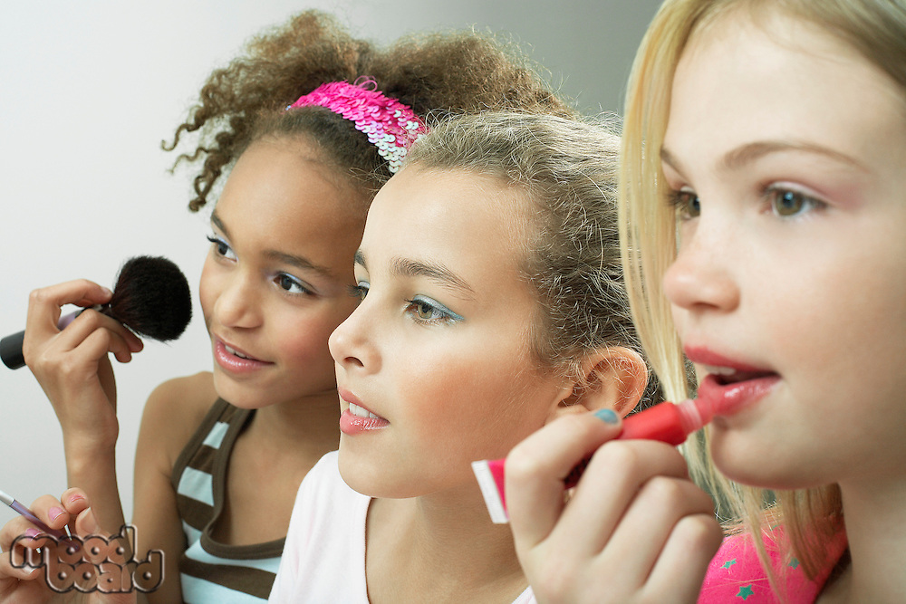 Girls standing side by side putting on make-up and lip gloss