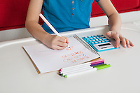Midsection of a girl writing in book doing homework