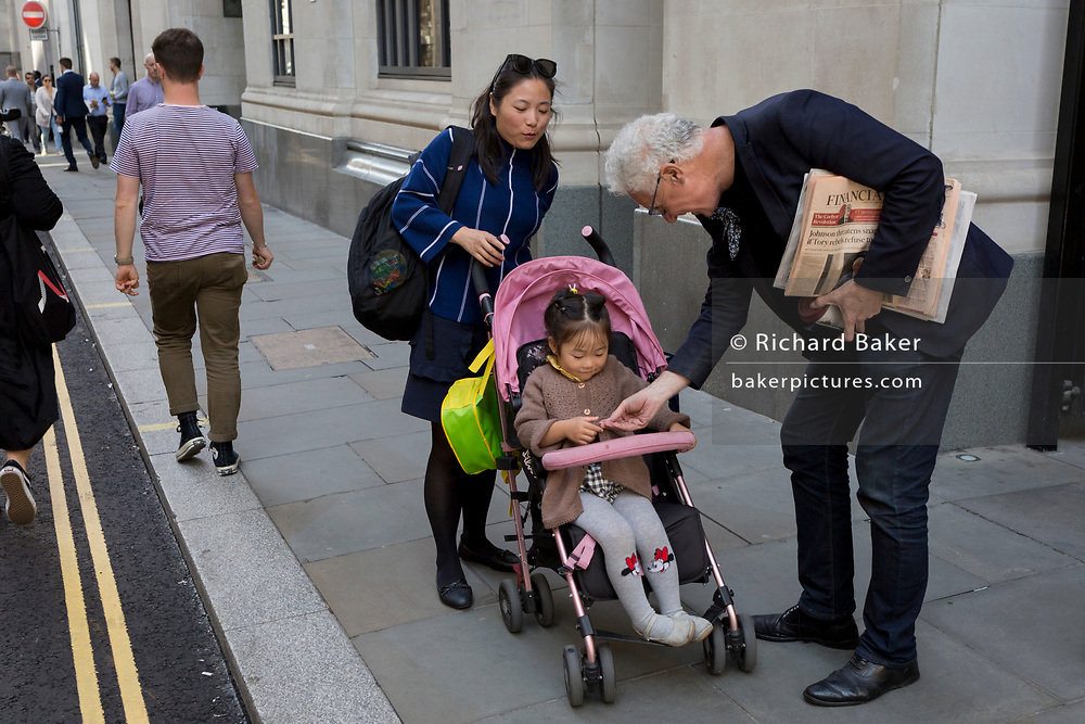 A businessman carrying the Financial Times stops to give something to a child on Lombard Street in the City of London, (aka The Square Mile) the capital's financial district, on 3rd September 2019, in London, England.