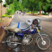 12-05-29   - LOME, TOGO -    Zemidjan ('take me quickly' in  Fon) driver Fousseni Kpe Kpassi demonstrates how he sleeps on his motorcycle in Lomé, Togo on May 29. Underpaid, rarely thanked and working all hours to make a meagre living, they find very few moments of calm and quiet in their lives. And so, the moto-taxi men have perfected various ways of calmly sleeping on their motorbike as they wait for  their next customer. And so, on the move amidst the chaos and bustle of daily life, they relax and sleep.  Photo by Daniel Hayduk