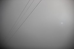 © Licensed to London News Pictures . 23/01/2019. Salford , UK . Electricity cables vanish in to thick fog and the sun is barely visible . Clear skies and snow shrouds the hills in the North West as fog descends over Manchester City Centre . Photo credit : Joel Goodman/LNP