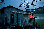 Solange Da Silva Correia prepares her family's fish dinner by the light of an oil lamp at the kitchen window of their riverside farmhouse near the town of Caviana, Amazonas, Brazil. (From the book What I Eat: Around the World in 80 Diets.) The caloric value of her day's worth of food on a typical day in the month of November was 3400 kcals. She is 49 years of age; 5 feet 2.5 inches tall; and 168 pounds.  With no indoor plumbing, she tackles anything messy on an overhanging counter, letting chickens and dogs clean up the scraps below.