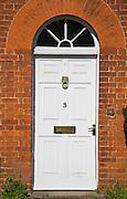 White door in red brick arch of building