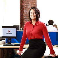 Corporate portrait taken in office environment with exposed red brick walls featuring business woman in red blouse and black skirt