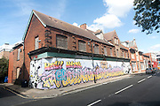 Painted hoarding boards around derelict shop buildings in Upper Orwell Street, Ipswich, Suffolk, England, UK