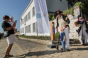 Belgium, Vieux-Genappe near Waterloo on 4th of June 2015. Official reopening of this former  farm, now a museum  where Emperor Napoleon and his staff spent the night of 17th June 1815. The last night before the battle of Waterloo.tourist taking a picture of a child and re-enactor