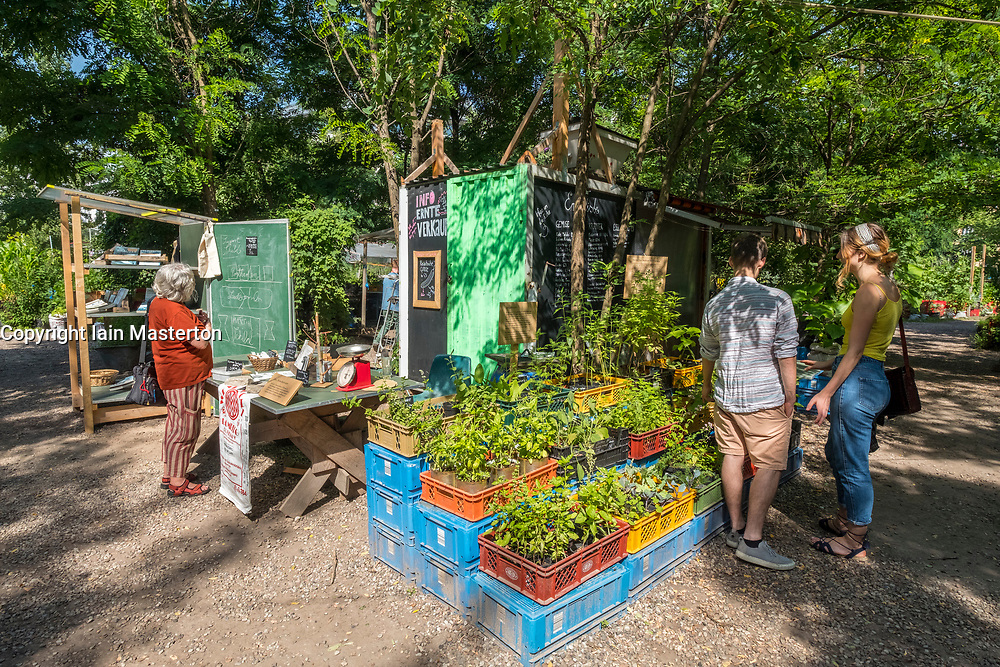 Stalls selling plants and books at  urban city community garden called Prinzessinnengarten in Kreuzberg, Berlin, Germany.