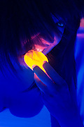 A portrait of a woman biting into a glowing Twinkie.Black light
