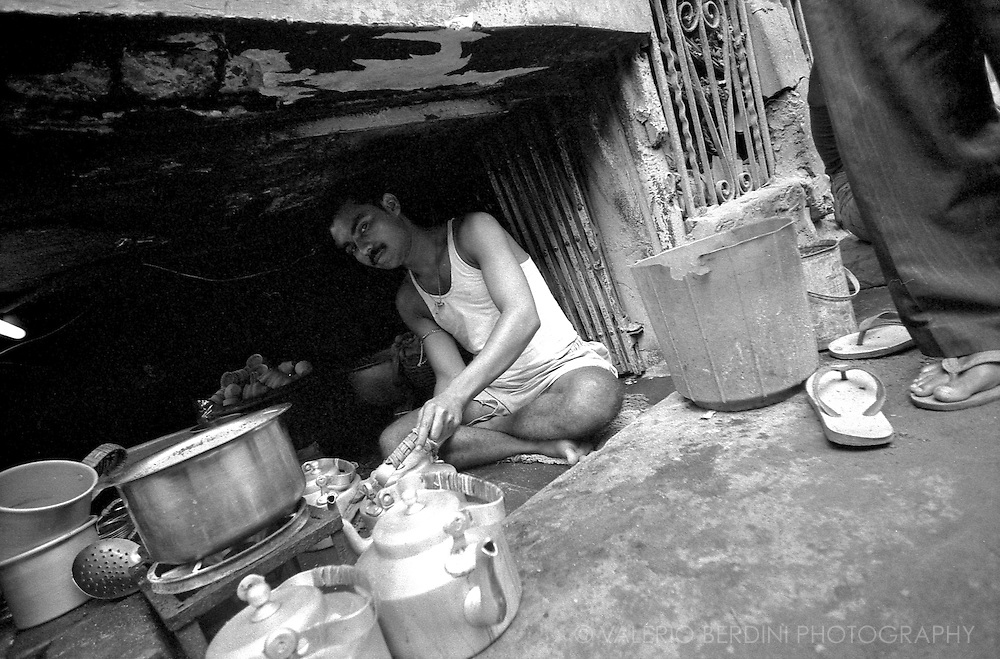 A tea sellers in a cavity below a pavement. Chai is sold in small glasses