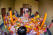 """09 FEBRUARY 2013 - BANGKOK, THAILAND: People make offerings in a chapel in Wat Mangkon Kamalawat, the largest Chinese temple in Chinatown in Bangkok. Bangkok has a large Chinese emigrant population, most of whom settled in Thailand in the 18th and 19th centuries. Chinese, or Lunar, New Year is celebrated with fireworks and parades in Chinese communities throughout Thailand. The coming year will be the """"Year of the Snake"""" in the Chinese zodiac.    PHOTO BY JACK KURTZ"""