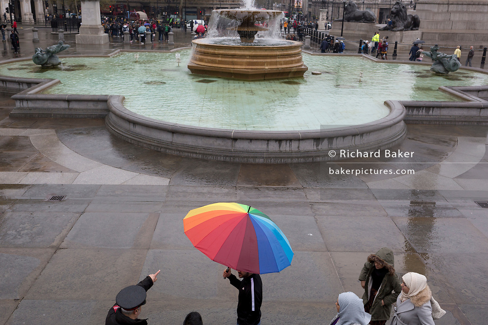 An official Heritage Warden points out places of interest to a middle-eastern family whose colours of the spectrum are on their brolley while visiting Trafalgar Square, Westminster, on 9th April 2019, in London, England.