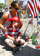 Casen Beyea, 3, wearing a toy fireman's helmet pauses at the cross for Andrew Ashcrast with his mother Christine at a memorial in Prescott, Arizona to firefighters killed in the nearby wildfire July 2, 2013.   An elite squad of 19 Arizona firemen was  killed in the worst U.S. wildland firefighting tragedy in 80 years apparently outflanked and engulfed by wind-whipped flames in seconds, before some could scramble into cocoon-like personal shelters on June 30, 2013. Beyea was a friend at school with Ashcraft. REUTERS/Rick Wilking (UNITED STATES)