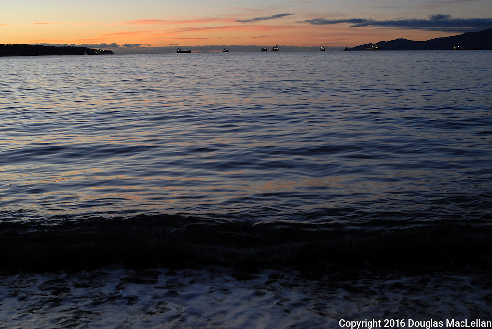 Vancouver BC, December 2016. Ships are anchored as the sun sets over English Bay in Vancouver, British Columbia, Canada.
