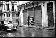 Old car passing in the street as it starts to rain.<br />