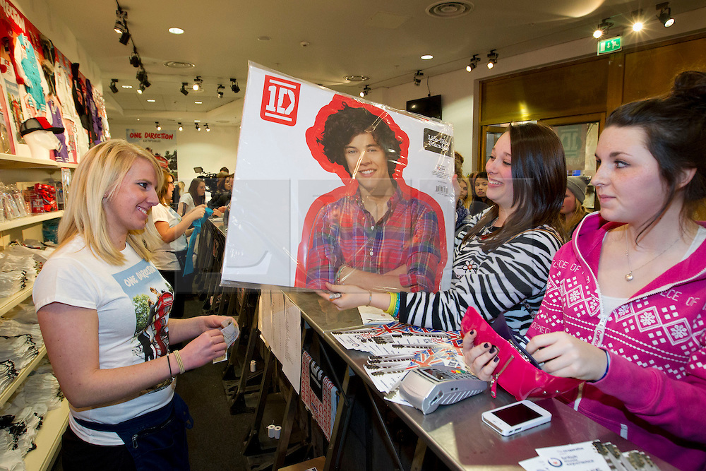 © Licensed to London News Pictures. 28/03/2013. London, UK. Store staff serve One Direction fans in the 'One Direction World' pop-up shop which opened today (28/03/2013) at the O2 dome in Greenwich London today. Photo credit: Matt Cetti-Roberts/LNP