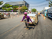 "15 FEBRUARY 2016 - ARANYAPRATHET, SA KAEO, THAILAND:  A Cambodian porter in Aranyaprathet pulls a load of bottled water to the Cambodian side of the border. Thais selling bottled water in the border town of Aranyaprathet, opposite Poipet, Cambodia, have reported a surge in sales recently. Cambodian officials told their Thai counterparts that because of the 2016 drought, which is affecting Thailand and Cambodia, there have been spot shortages of drinking water near the Thai-Cambodian and that ""water shortages in Cambodia had prompted people to hoard drinking water from Thailand.""    PHOTO BY JACK KURTZ"