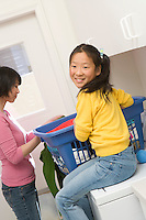 Mid-adult woman and her daughter preparing clothing in laundry room