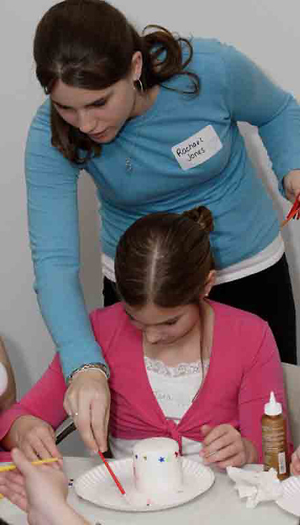 Rachael Jones, from Waynesville, helps Tara Nix, 8, from Waynesville mix some paint to put on a candle at the American Girl Tea Party, Saturday, January 27, 2007 in Waynesville's Mary L. Cook Library.  Tara will be able to take the candle home at the end of the party.