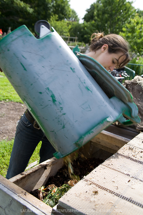 A young, healthy woman adding compost ingredients to a pile in a community garden.
