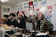 During the Jewish festival of Purim a group of Orthodox Jewish boys from the Viznitz Yeshiva (school) in fancy dress visit local businessmen to collect money for their school. At the end of the day they return to their school and have a celebration feast, the Purim Rabbi performs a song to his class during the meal. Large amounts of alcohol are consumed during the festival.