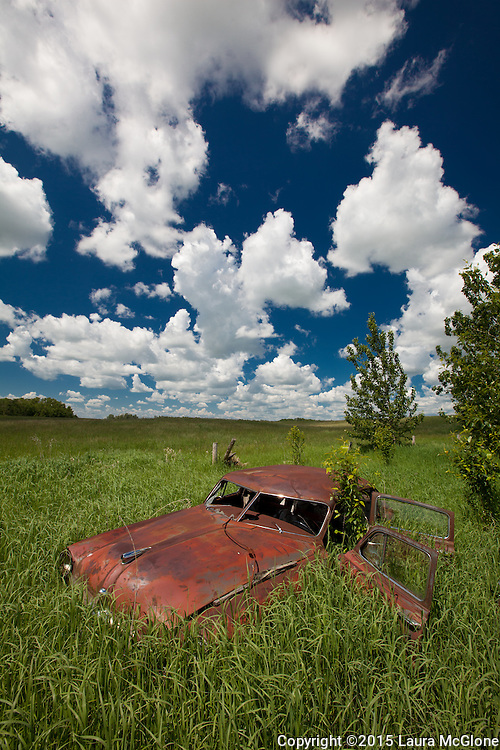 Abandoned car in Field with Dramatic Clouds, Alberta Canada