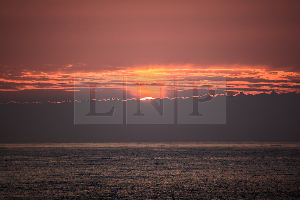 © Licensed to London News Pictures. 24/06/2015. Whitley Bay.UK. Picture shows the sun rising over Whitley bay. Forecasters are predicting a dry but cloudy day with sunny spells this morning. Photo credit : Andrew McCaren/LNP