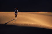 Image of a woman hiking on the dunes at White Sands National Monument in New Mexico, American Southwest, model released