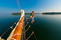 Girls jumping off the bow of the Schooner Nathaniel Bowditch into the cold waters of Holbrook Bay (part of Penobscot Bay), Maine USA