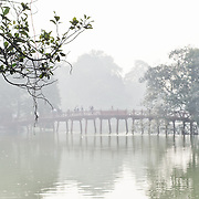 Morning haze partly obscures The Huc Bridge (Morning Sunlight Bridge). The red-painted, wooden bridge joins the northern shore of the lake with Jade Island and the Temple of the Jade Mountain (Ngoc Son Temple).